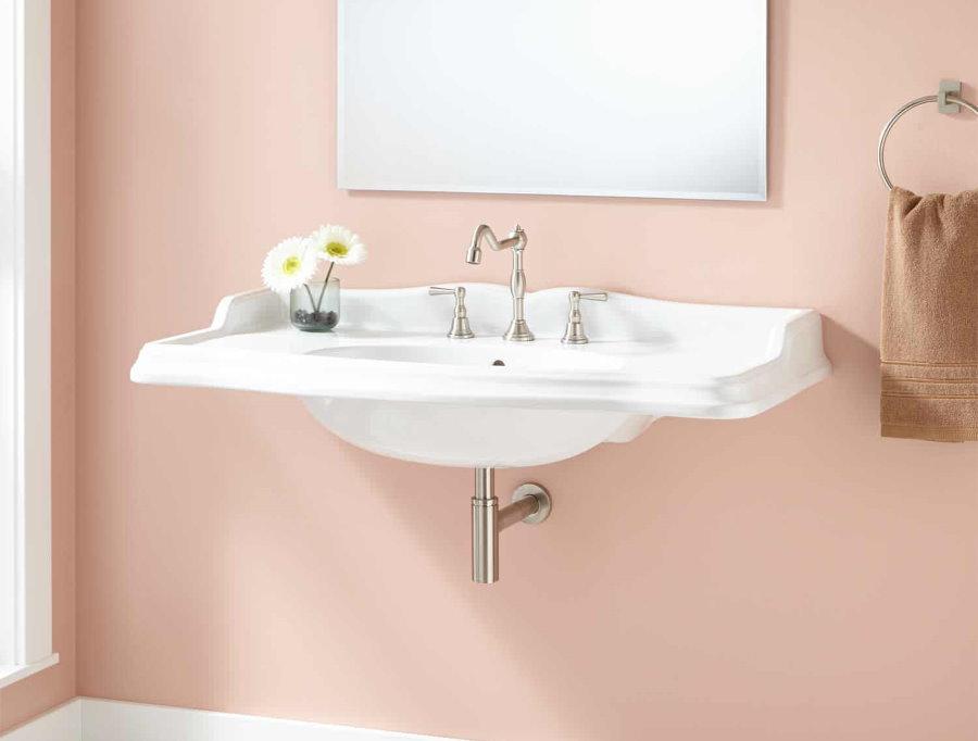 Белая подвесная раковина на розовой стене в ванной