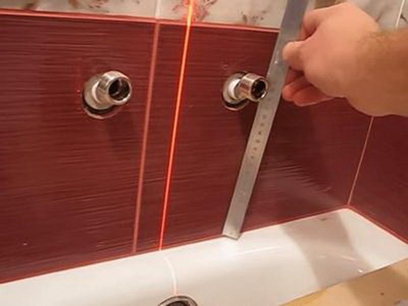 Замер линейкой высоты крепления смесителя в ванной