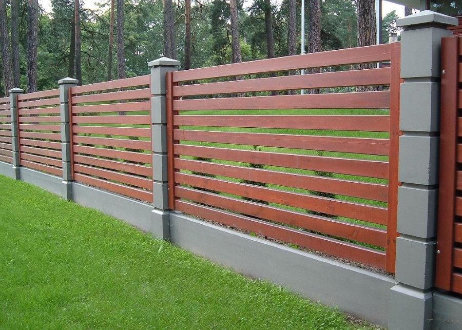 Деревянный забор на серых бетонных столбах