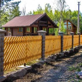 Деревянная ограда с бетонными столбами