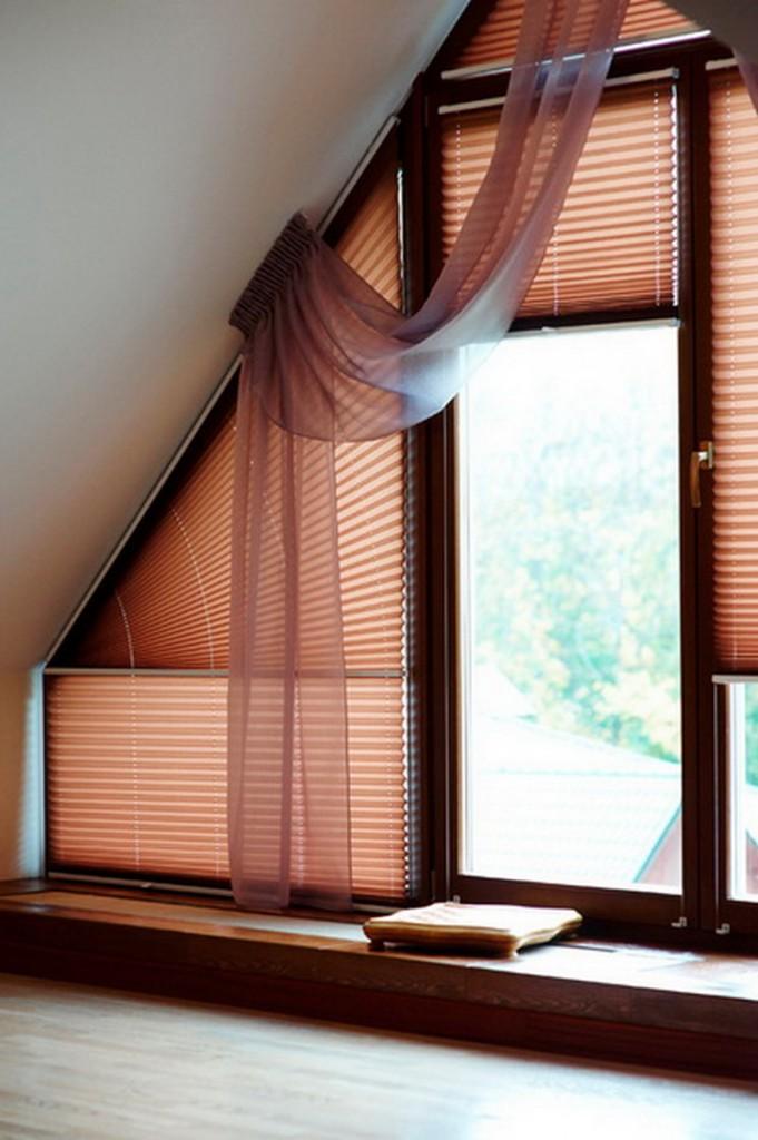 Розовые шторы из бумаги на окне в мансарде частного дома