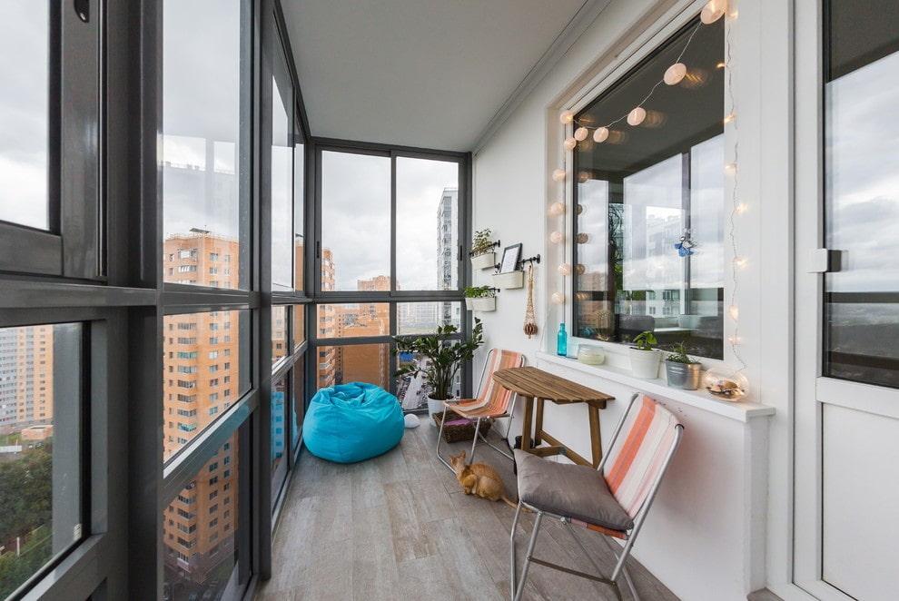 Интерьер просторного балкона с большими окнами