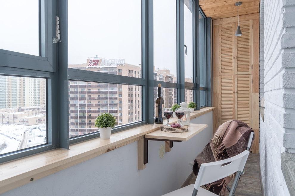 Подвесной столик на балконе с серыми рамами