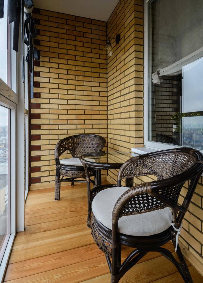 Плетенные стульчики на балконе кирпичного дома