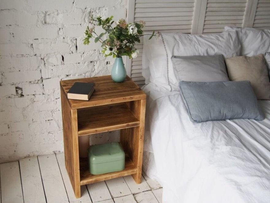 Простая тумбочка из дерева возле кирпичной стены