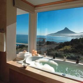 Встроенная ванна перед окном с красивым видом