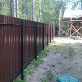 Забор с винтовыми столбами вдоль деревянного дома