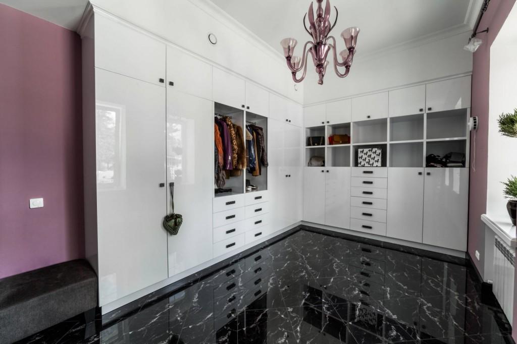Белая глянцевая мебель в гардеробной угловой планировки