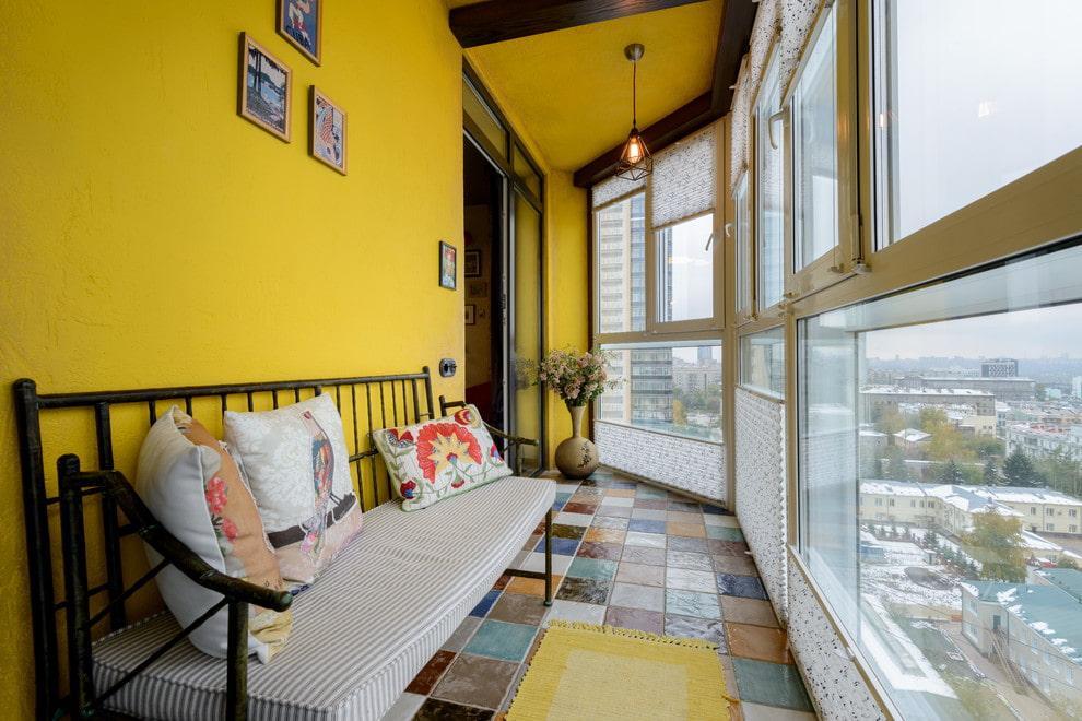 Узкая скамейка вдоль желтой стены балкона