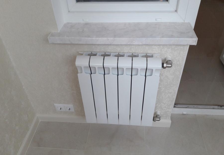 Белый радиатор отопления под подоконником на лоджии
