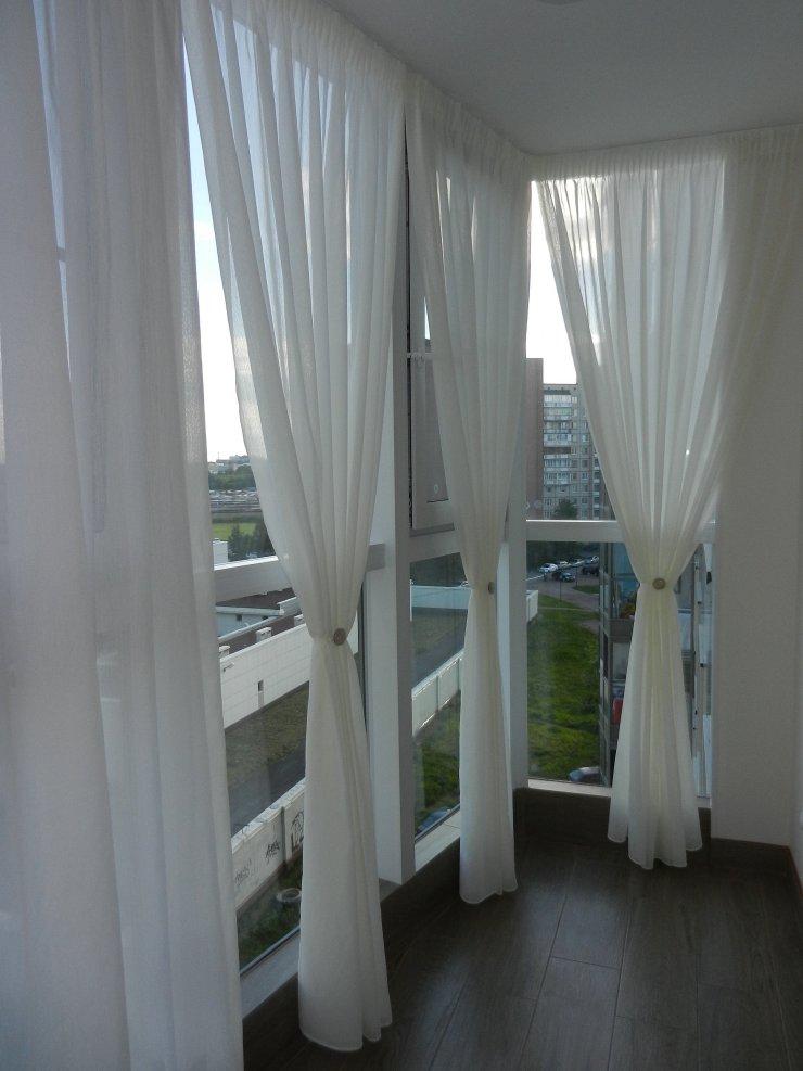 Длинные шторы белого цвета на балконе