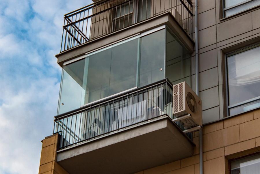 Фото снаружи балкона с безрамным остеклением