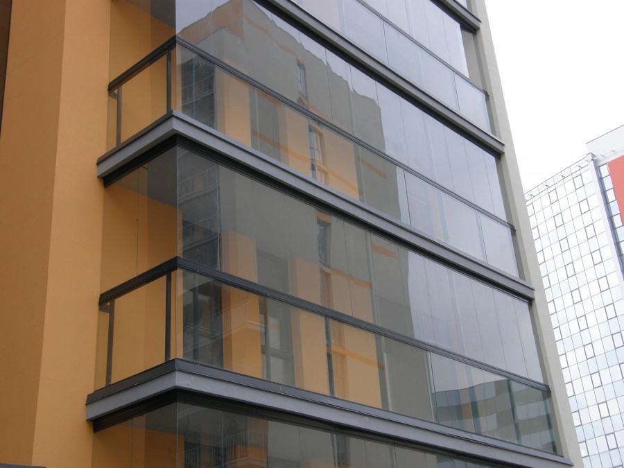 Длинный балкон с окнами без рам