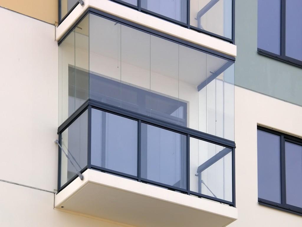 Вид снаружи на балкон с безрамным остеклением