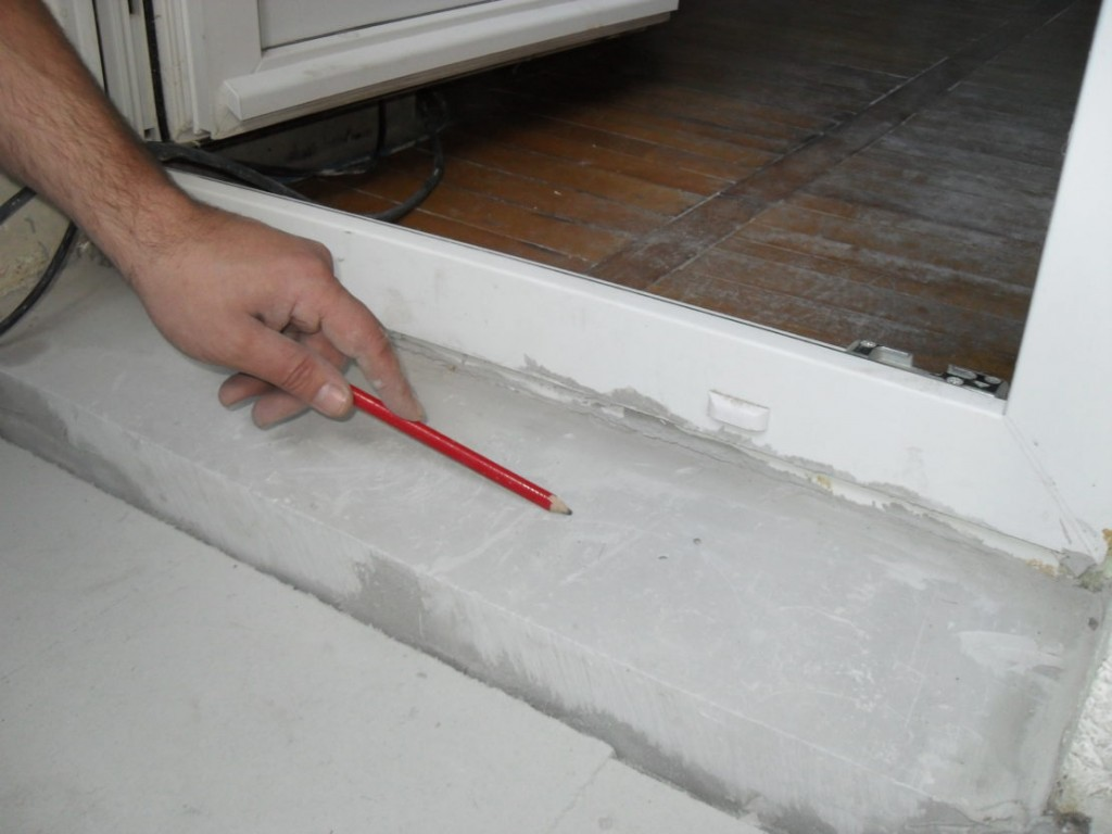 Цементный порог перед пластиковой дверью на балконе