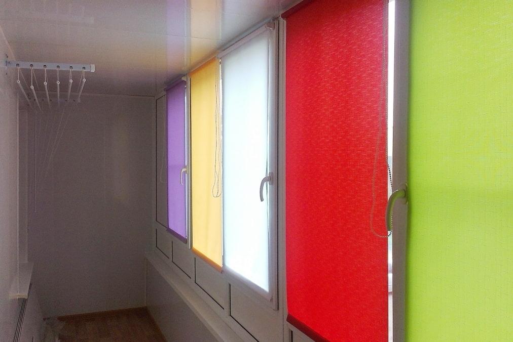 Разноцветные рулонные шторы на окнах балкона