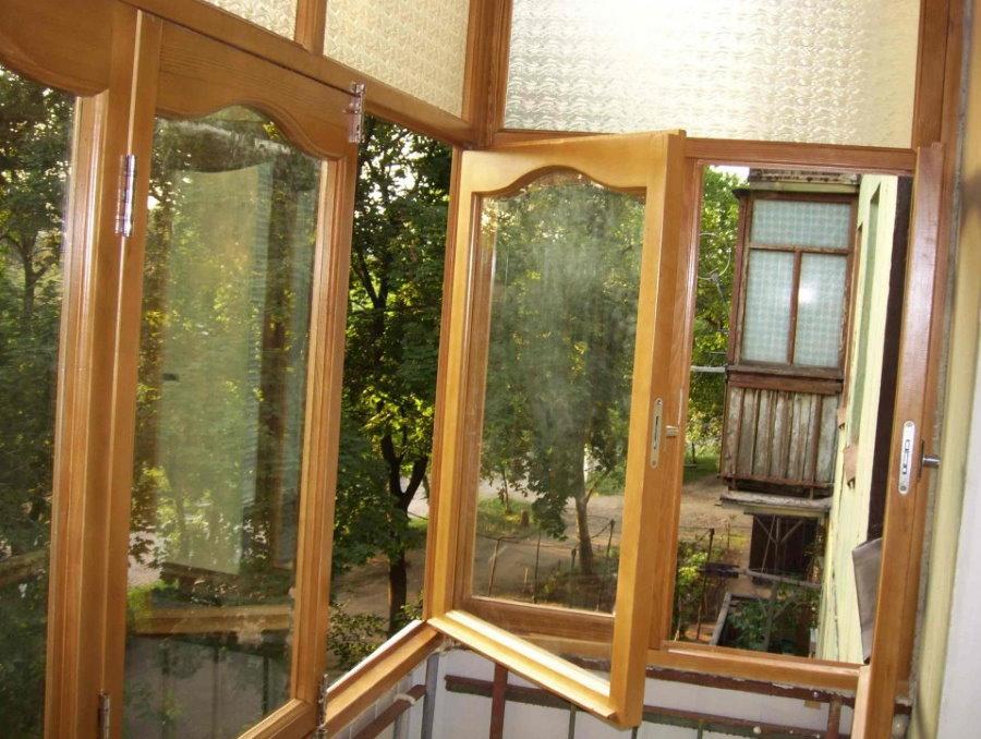 Открытые створки деревянного окна на балконе