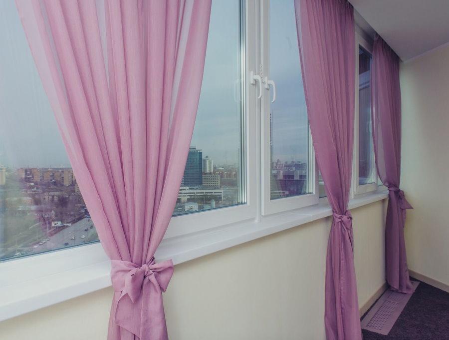 Розовые шторы на окнах утепленного балкона