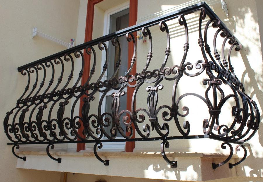 Небольшой балкон с дутым кованным ограждением