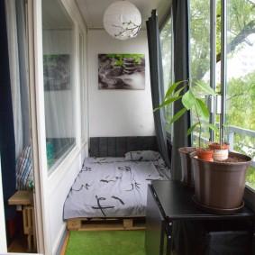 Зеленый коврик перед кроватью на лоджии