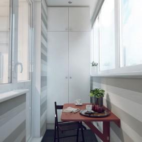 Небольшой столик из фанеры на стене балкона