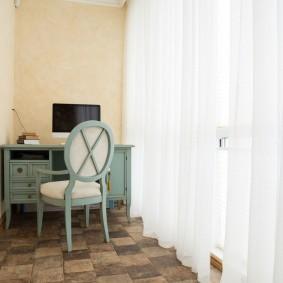 Деревянный столик на балконе с белыми шторами