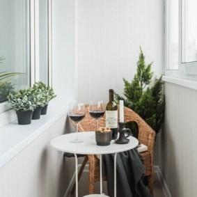 Плетенное кресло и белый столик на балконе