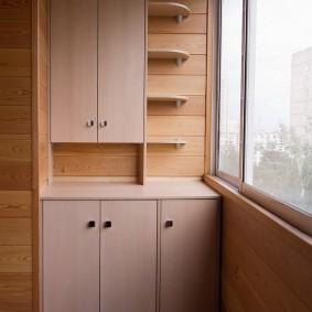 Удобные шкафчики на балконе с обшивкой вагонкой