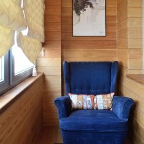 Темно-синее кресло на лоджии с деревянной обшивкой