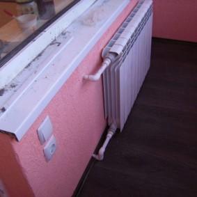Белый радиатор отопления на розовой стене