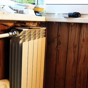Радиатор отопления на стене с деревянной отделкой