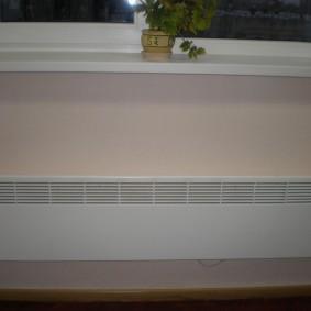 Длинный конветор на стене теплого балкона