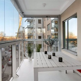 Деревянный стол для обедов на остекленном балконе