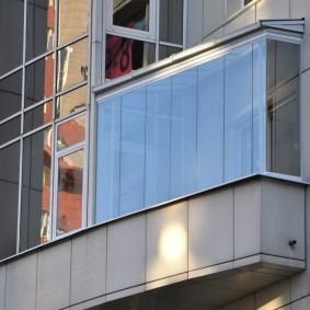 Фасад многоэтажного дома с безрамным остеклением балкона