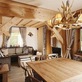 Люстра с рогами над деревянным столом