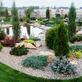 Садовый рокарий вокруг небольшого водоема