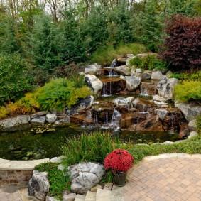 Каменный водопад в саду природного стиля