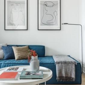 Синий диван под картинами в гостиной