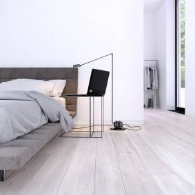 Ноутбук на столике возле низкой кровати