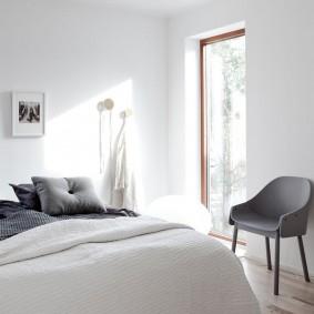 Серое кресло около окна спальни