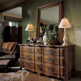 Зеркало в раме на деревянном комоде