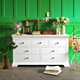 Белый комод на фоне зеленой стены