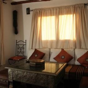 Светлые шторы вгостиной комнате среднего размера