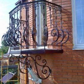 Маленький кованный балкон на кирпичном фасаде