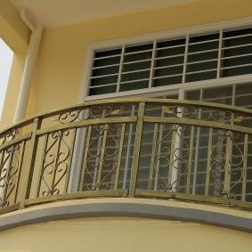 Современный балкон с кованными перилами