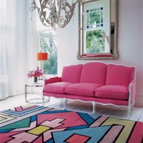 Яркий ковер перед розовым диваном