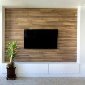 Черный телевизор на стене с ламинированными панелями