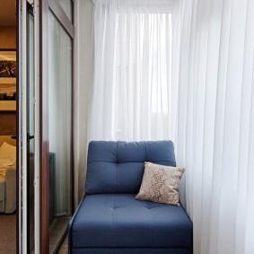 Синее кресло на балконе с длинными шторами
