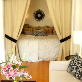 Светлые шторы над кроватью в гостиной