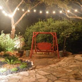 Гирлянда с открытыми лампочками над садовыми качелями